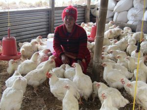 ETC women's group member at her poultry farm, 2019